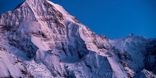Monch at sunset tinged pink in Grindelwald ski resort, Switzerland
