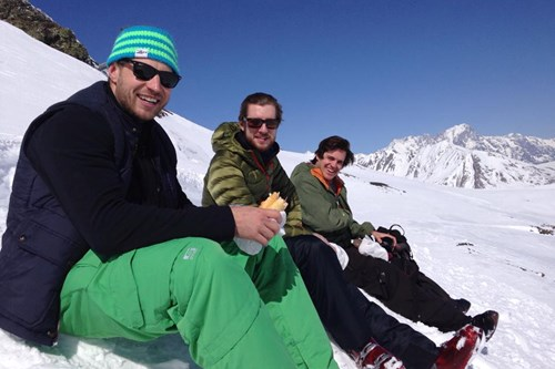 three men enjoy a sandwich on the slopes