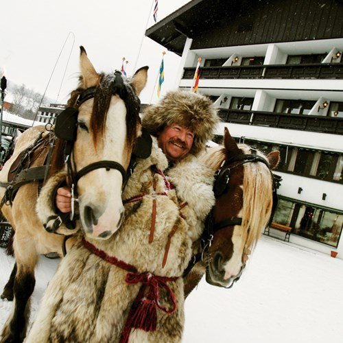 happy man in fur hat on horse sleigh outside Hotel Bardola, Norway