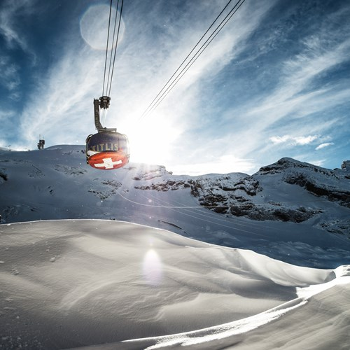 rotating cable car over snow slopes and blue skies in engelberg