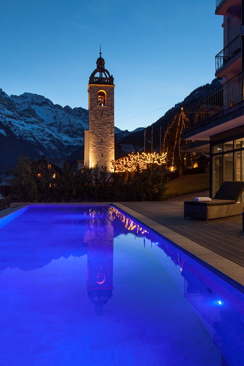 Outdoor pool lit up at night Hotel National in Champery