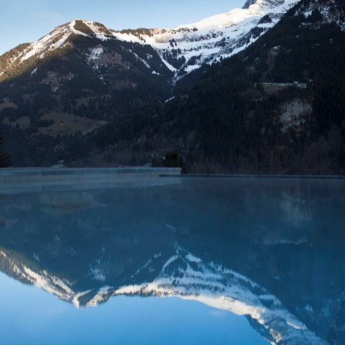 Outdoor pool with mountain views at Hotel National in Champery