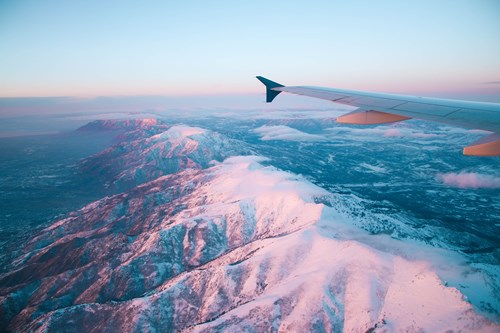 plane flying over mountains ski more sustainably