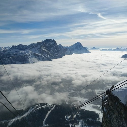 mountains from above clouds below chairlift