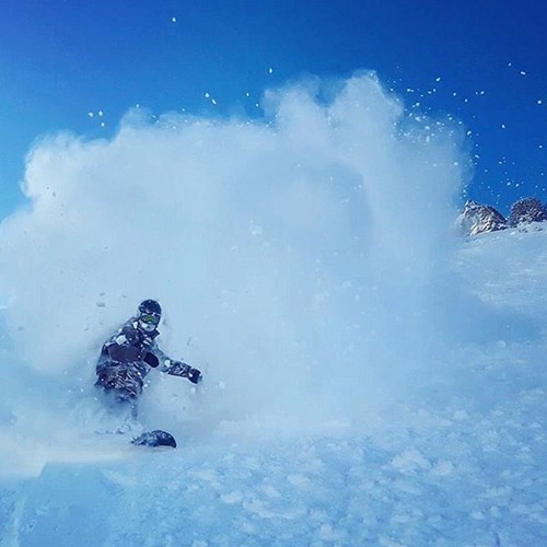 snowboarder kicking up powder cloud on slopes