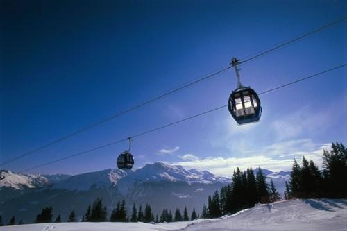 Skiing in Klosters village, gondola in blue skies