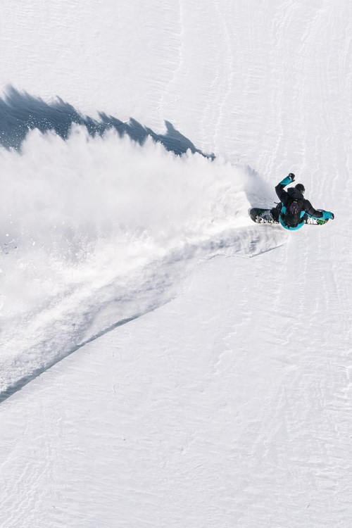 Birds eye view of a snowboarder shredding powder in Courmayeur