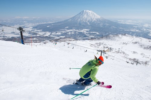 Skiing in Niseko with a view of Mt Yotei, Skiing in Japan, blue skies