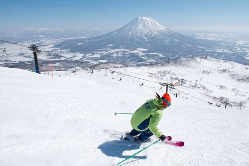 Skiing in Niseko with a view of Mt Yotei, Skiing in Japan, blue skies