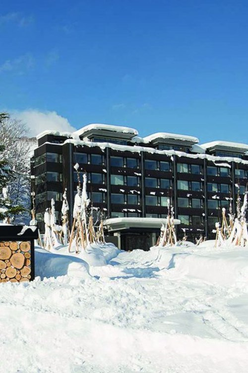 Ski Hotel Ki Niseko - Ski Japan - exterior in snow with blue skies