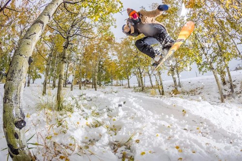 Aspen Snowmass boarder jumping through trees