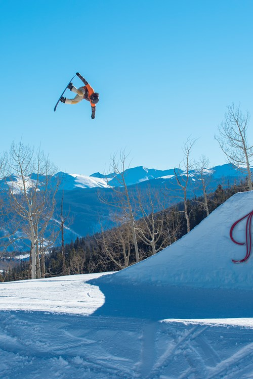 aspen sign snowboarder jumping