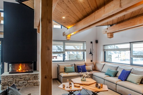 lounge area with roaring fire in the chalet des cascades, les arcs